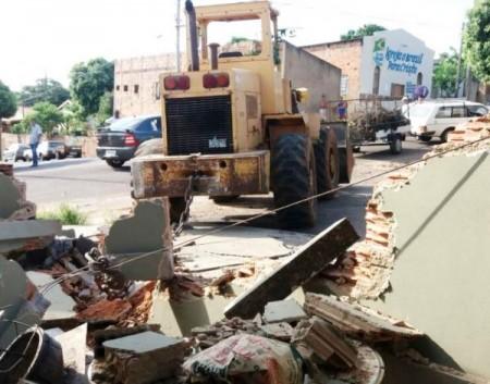 Pá-carregadeira desgovernada atinge veículo e pára após destruir muro